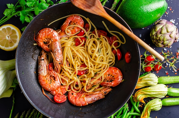 Italian pasta cooking with tiger prawns or shrimps with vegetables.