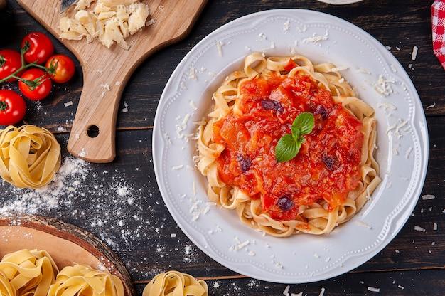 토마토 소스를 곁들인 이탈리아 파스타 요리. 요리 준비를 위한 재료로 구성된 구성입니다.