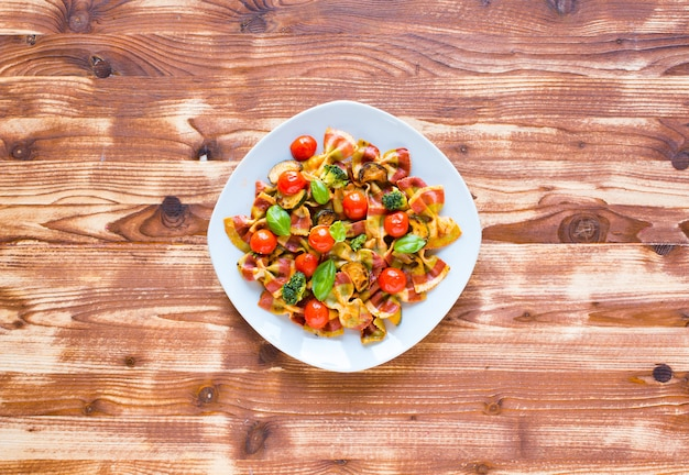 Italian pasta farfalle in tomato sauce and various type of vegetables on a wooden background