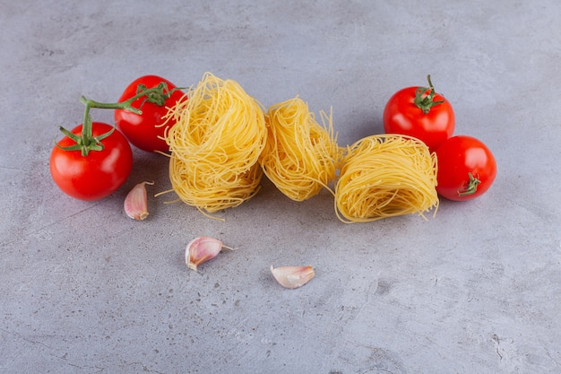 Italian pasta fettuccine nest with fresh red tomatoes and cloves of garlic.