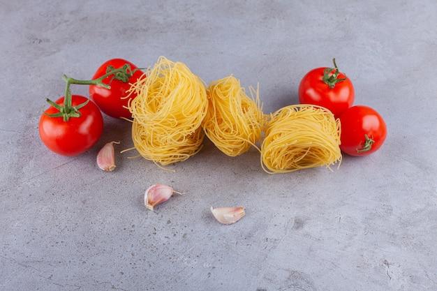 Nido di fettuccine di pasta italiana con pomodori rossi freschi e spicchi d'aglio.