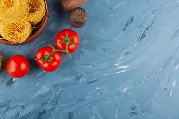 Nido di fettuccine di pasta italiana con pomodori rossi freschi e spezie.