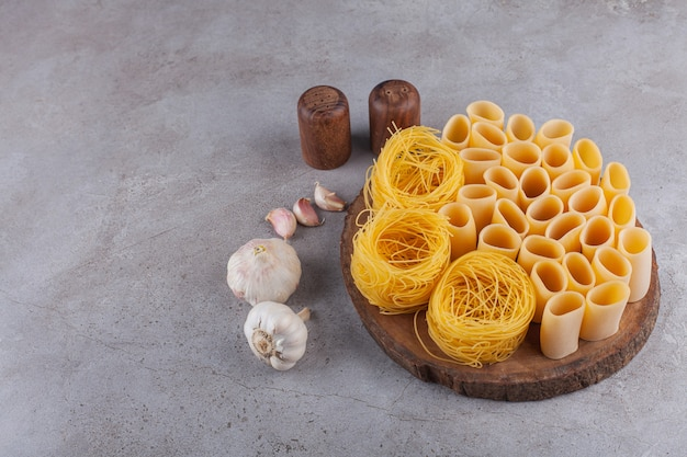 Italian pasta fettuccine nest with uncooked tube macaroni on a wooden piece .