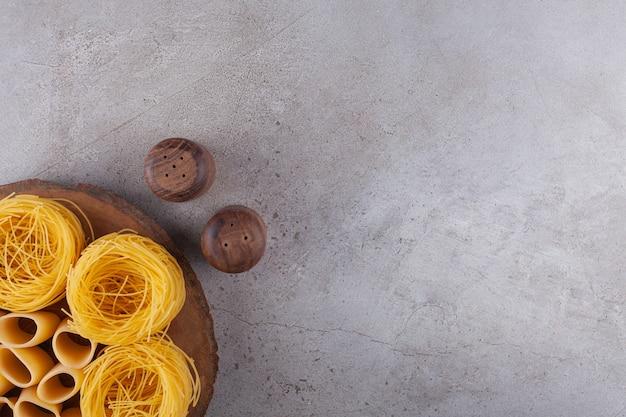 Fettuccine di pasta italiana nido con maccheroni tubo crudo su un pezzo di legno.