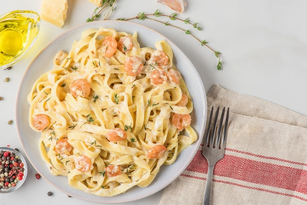 Italian pasta fettuccine or tagliatelle with shrimps in a creamy sauce with parmesan cheese and thyme in a plate