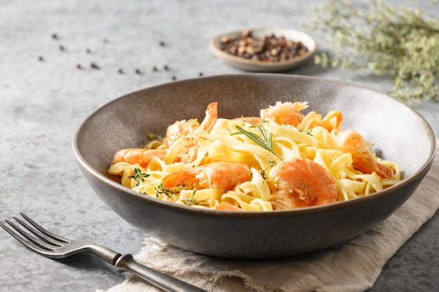 Italian pasta fettuccine with shrimps decorated rosemary sprig in bowl on gray table. close up.