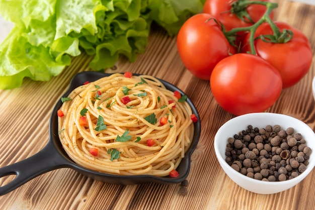 Italian pasta in a frying pan on a light wooden background with seasonings and vegetables.