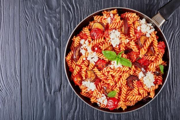 Итальянская паста fusilli alla norma с баклажанами, помидорами, базиликом, сыром рикотта в сковороде на черном деревянном столе