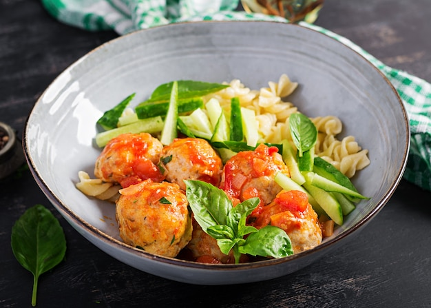 Italian pasta. fusilli with meatballs, cucumber and basil on dark background. dinner. slow food concept.