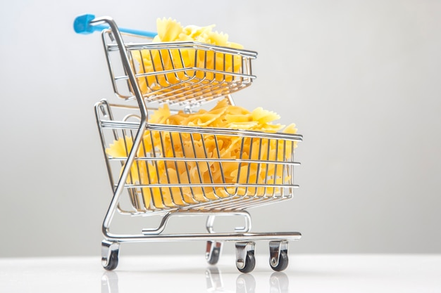 Italian pasta in a grocery basket from the market on a white background. flour products and food in cooking