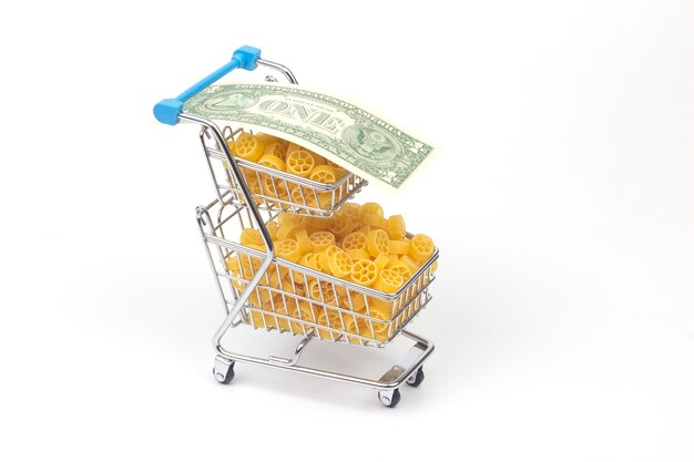 Italian pasta in a grocery basket from the market with a dollar bill. flour products and food in cooking