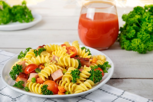 이탈리아 파스타, 햄, 야채와 토마토 주스 한잔. 균형 잡힌 식사.