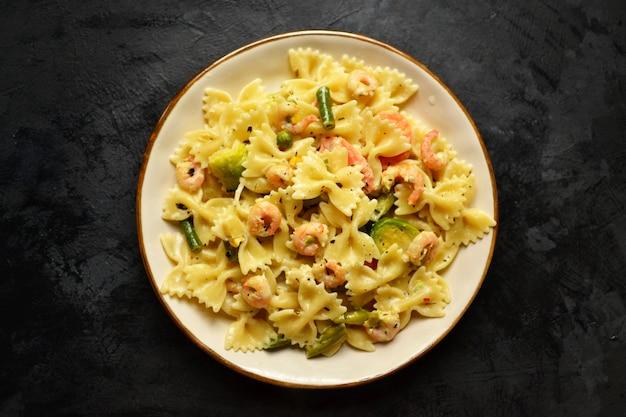 Итальянская паста в сливочном соусе с креветками на тарелку, вид сверху. фарфалле с креветками на темном столе.