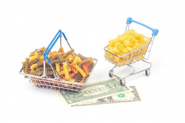 ドル紙幣と市場からの食料品バスケットのイタリアンパスタ。小麦粉製品と調理中の食品