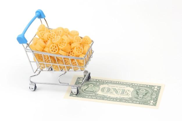 白い背景の上のドル紙幣と市場からの食料品バスケットのイタリアンパスタ。小麦粉製品と調理中の食品