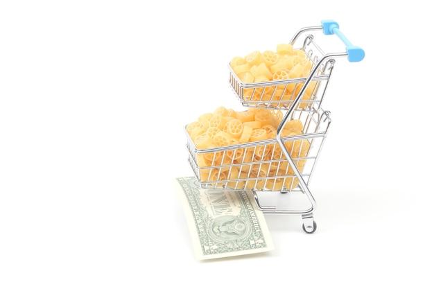 白い表面にドル紙幣が付いている市場からの食料品バスケットのイタリアンパスタ。小麦粉製品と調理中の食品