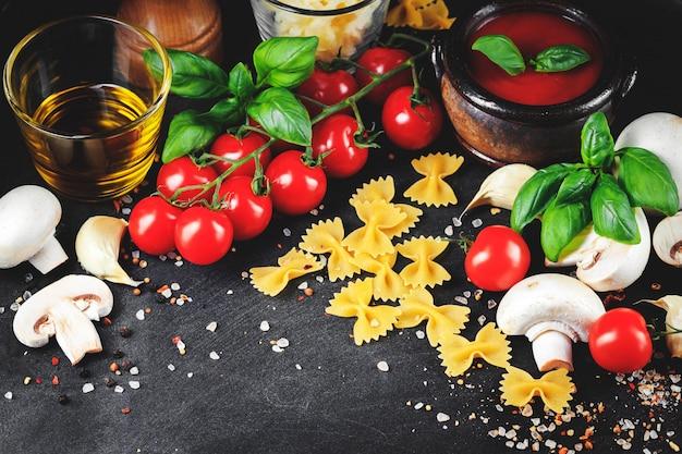 イタリアのパスタの材料。チェリートマト、ファルファッレパスタ、ニンニク、マッシュルーム、バジル、オリーブオイル、モッツァレラチーズ、暗いグランジ背景のスパイス