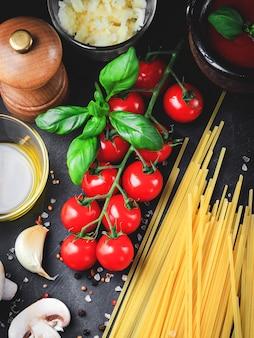 イタリアのパスタの材料。チェリートマト、スパゲッティパスタ、ニンニク、マッシュルーム、バジル、オリーブオイル、モッツァレラチーズ、暗いグランジ背景のスパイス