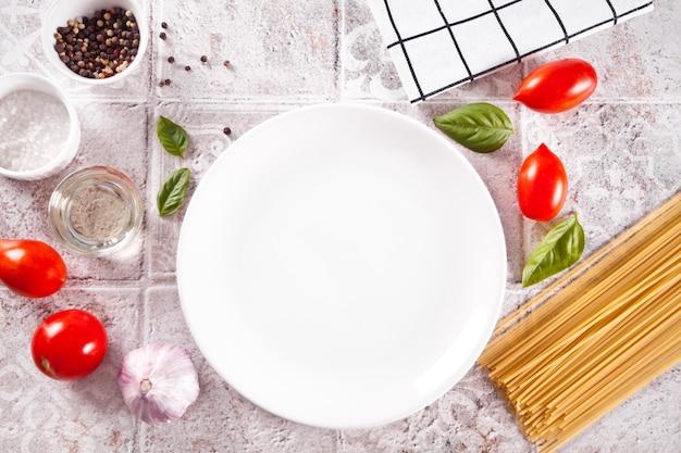 白い空のプレートとテーブルの上のイタリアンパスタの材料。フードクッキング。上面図。スペースをコピーします。