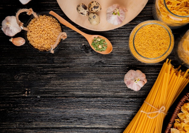 Italian pasta linguini fellini farfalle farfallini stelline garlic eggs dry herbs top view copy space
