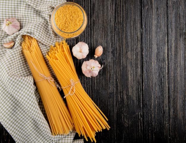 Italian pasta linguini spaghetti garlic on the dark wooden background top view copy space