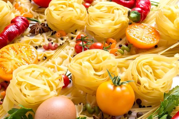 スパイス、赤唐辛子、鶏の卵、白地に黄色と赤のトマトと様々な種類のイタリアのパスタ。イタリア料理のパスタとソースを調理するコンセプト