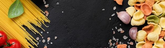 黒の背景に調理食品の伝統的な食材を使用したイタリアンパスタオレキエッテ。料理の料理の背景。上面図