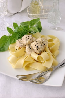 Italian pasta - pappardelle with chicken fillet in a creamy sauce with sesame seeds