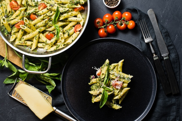 Italian pasta penne with spinach, cherry tomatoes and basil.