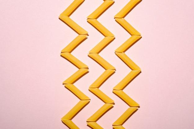 이탈리아 파스타, 핑크 테이블에 원시 펜 네 튜브 마카로니 지그재그, 상위 뷰 복사 공간, 추상 음식