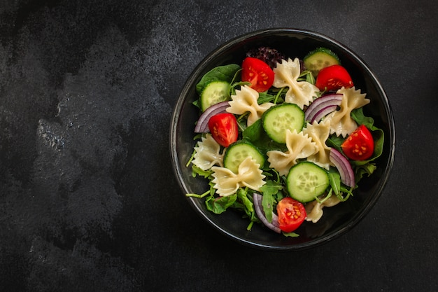 Italian pasta salad farfalle, vegetables, mix leaves, top view