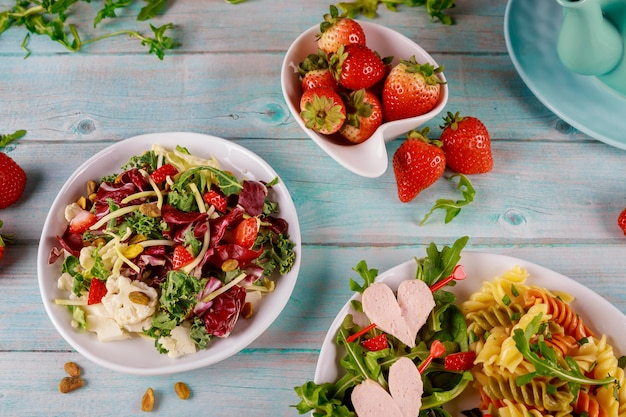 Italian pasta salad with heart sausage and salad on wooden table