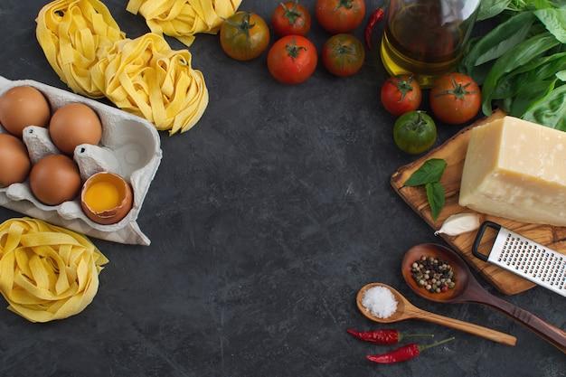 Italian pasta and sauce ingredient  top view on dark background
