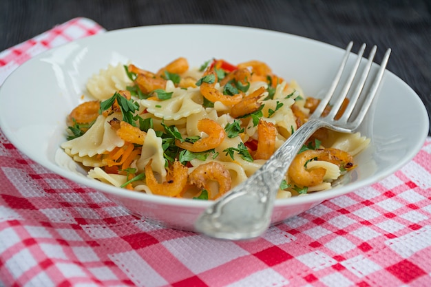Italian pasta in a sauce with shrimps on plate, top view.