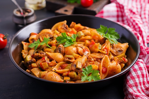 Italian pasta shells with mushrooms, zucchini and tomato sauce.