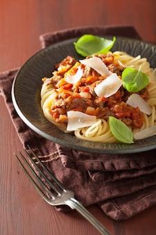 Итальянская паста спагетти болоньезе с базиликом на деревенском столе