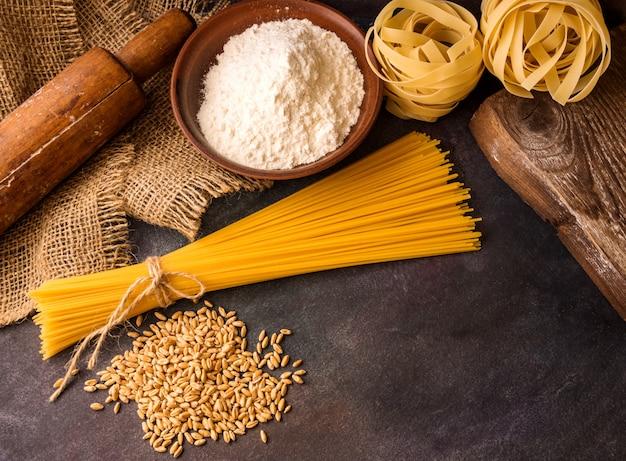 イタリアのパスタ、スパゲッティ、フェットチーネ、小麦、麺棒、織り目加工の背景に小麦粉。