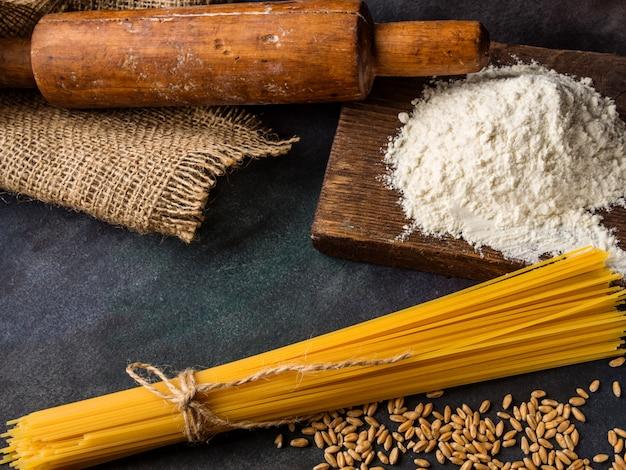 イタリアのパスタ、スパゲッティ、小麦、麺棒、織り目加工の背景に小麦粉。