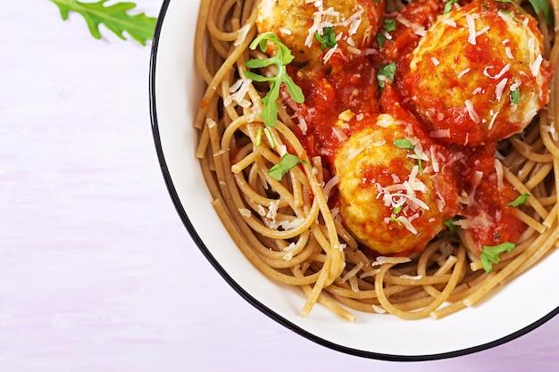 Итальянская паста. спагетти с фрикадельками и сыром пармезан в миску на светлом деревенском деревянном столе. ужин. вид сверху. концепция медленной еды
