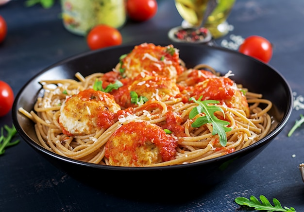 Italian pasta. spaghetti with meatballs and parmesan cheese in black plate on dark rustic wood table.  dinner. slow food concept