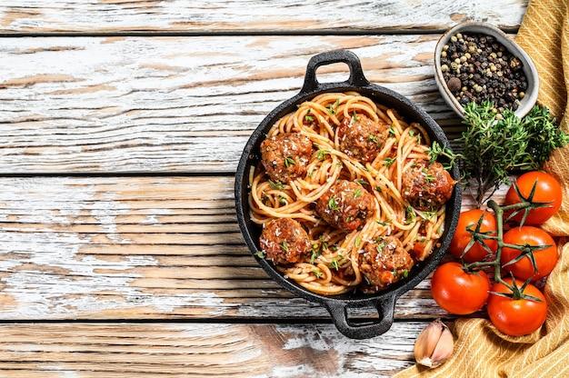 イタリアのパスタスパゲッティ、トマトソースとミートボールの鋳鉄鍋にパルメザンチーズを添えて。白い木の背景。上面図。スペースをコピーします。