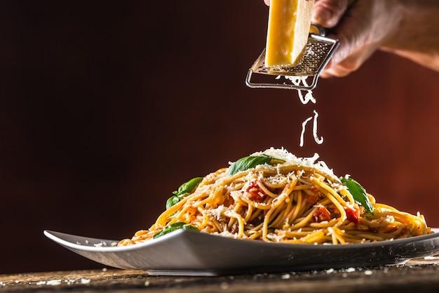 하얀 접시에 토마토 소스 바질과 파마산 치즈를 넣은 이탈리아 파스타 스파게티.