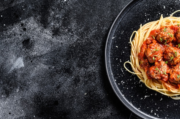 Italian pasta spaghetti with tomato sauce and meatballs. black background. top view. copy space.