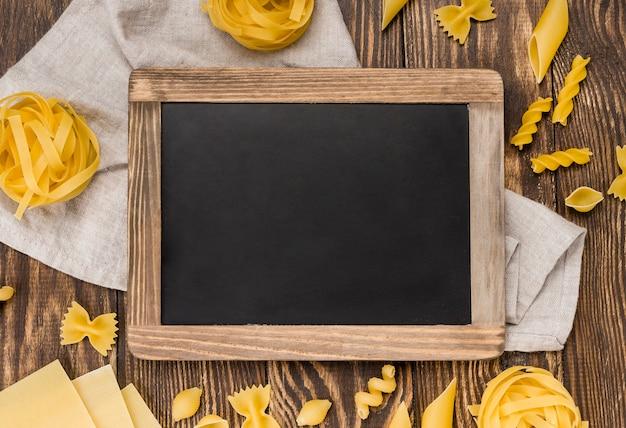 Italian pasta in spoons beside chalkboard