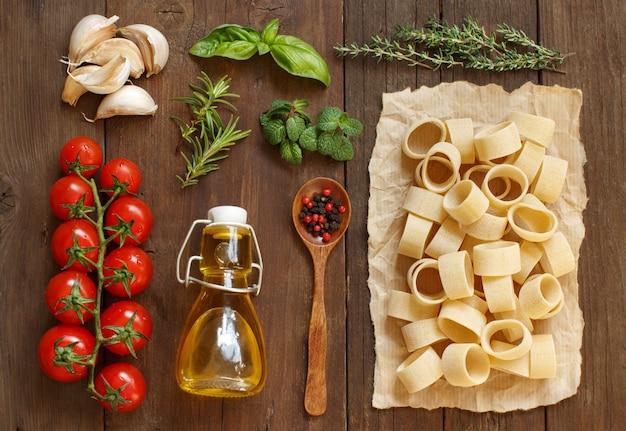 イタリアのパスタ、野菜、ハーブ、オリーブオイル、木製のテーブル、トップビュー