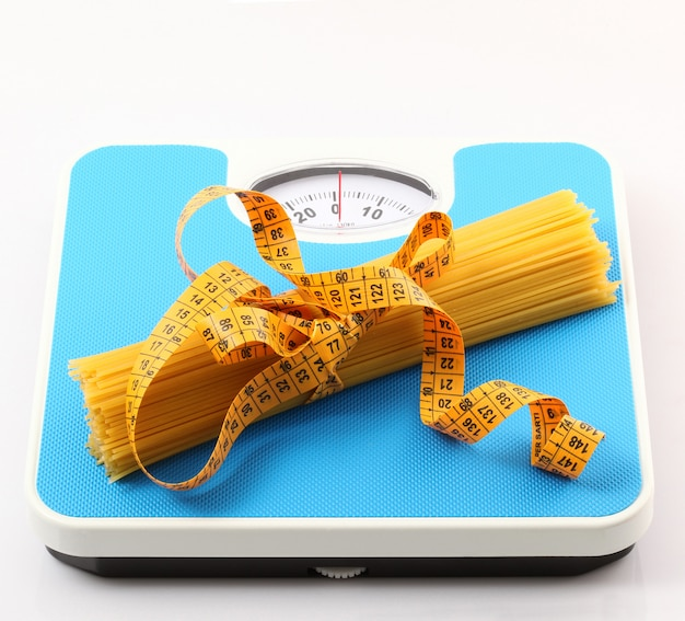 Italian pasta on white background with bathroom scale