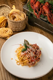 Italian pasta with boiled crayfish and sauce on a wooden farm table