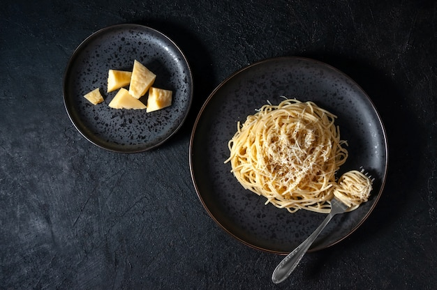 Italian pasta with cheese and pepper on black plate on dark background