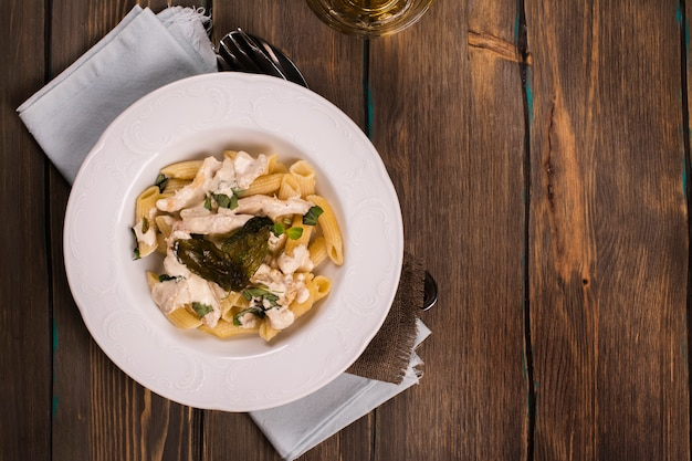 Italian pasta with chicken, cream sauce and basil over grunge wooden table.
