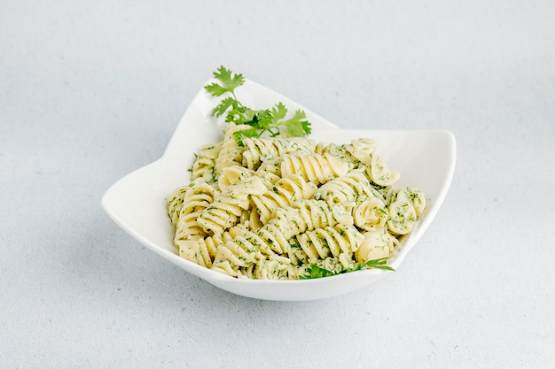 Italian pasta with green herbs in a white bowl.